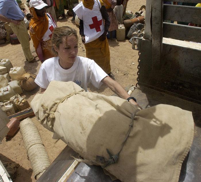 Juin 2004, Angelina Jolie aide les réfugiés à charger leurs maigres possessions sur le camion, près de Tiné, au Tchad, avant qu'ils ne partent pour les camps de l'UNHCR