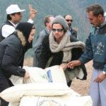 Novembre 2005, Angelina Jolie et Brad Pitt aident à décharger des sacs de nourriture de l'hélicoptère pour les survivants du séisme à Jabel Sharoon, au Cachemire pakistanais